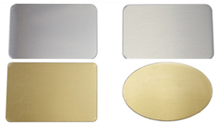 Image of two stainless rectangle nameplates, one brushed, one shiny and two brass nameplates, one rectangle, one oval.